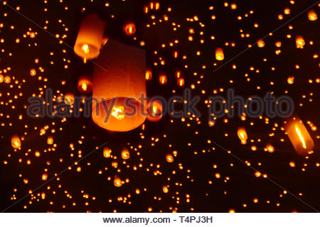 Releasing sky lanterns celebrating Yi Peng Lantern Festival, Chiang Mai, Thailand - Stock Photo