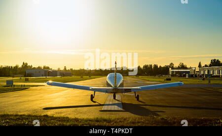 Small plane ready to take off at the airport at sunrise. - Stock Photo