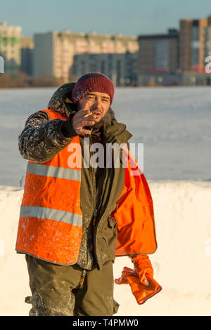 Portrait of a worker in a green jacket with a hood on his head in an orange reflective vest and a cigarette in his hand - Stock Photo