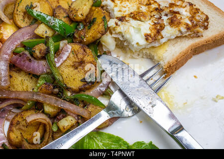 A set breakfast plate of hash brown potatoes, onions and fried egg on toast - Stock Photo