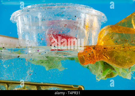 Crumpled used bag. Transparent food container floating on the water surface with bottles and bags around - Stock Photo