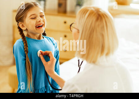 Breathing in. A cute nice pleasant long-haired girl taking a deep breath while a fair-haired appealing pediatrician in glasses checking her lungs. - Stock Photo