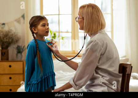 To see a doctor. A sweet pretty small girl with long braids breathing out while a short-haired charming female physician in glasses examining her lung - Stock Photo