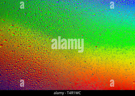 Drops of water against the background of the rainbow and with its reflection in them - Stock Photo