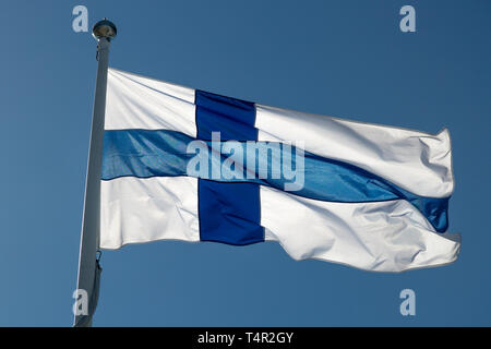 The Finnish Flag on a Flagpole waving in the wind with a blue sky. - Stock Photo