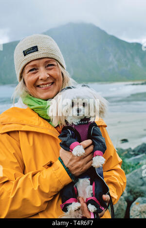 A portrait of a Scandinavian woman and her pet dog wearing a waterproof jacket in the wet weather landscape of Norway - Stock Photo