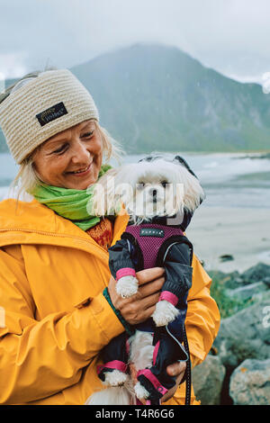 A portrait of a Scandinavian woman and her pet dog wearing a waterproof raincoat in the wet weather landscape of Norway - Stock Photo