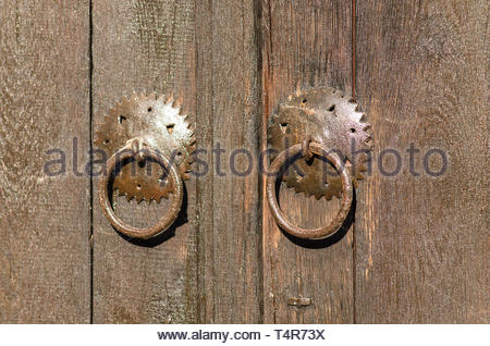 Old metal padlock on a wooden door. Historical village Bojenci, Gabrovo, Bulgaria. Old door lock. Old locked padlock with rings on old wooden board do - Stock Photo