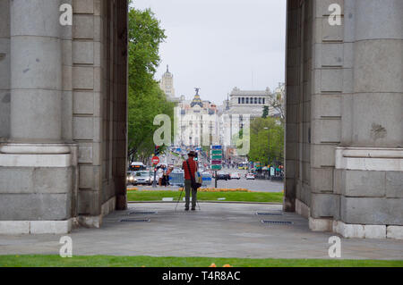 MADRID, SPAIN - APRIL 17: Tourists taking pictures at Puerta de Alcala at sunset on a cloudy dayon April 17, 2019 in Madrid, Spain. - Stock Photo