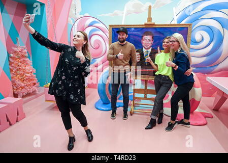 St Petersburg, Russia. 18th Apr, 2019. ST PETERSBURG, RUSSIA - APRIL 18, 2019: Visitors take a selfie at a 15kg picture showing a likeness of Ukraine's presidential candidate Volodymyr (Vladimir) Zelensky with the national Ukrainian colours behind, made from some 3,000 Roshen sweets, at Sladky (Sweet) Museum at Nevsky Prospekt in St Petersburg; Roshen is a confectionery corporation owned by Ukraine's incumbent president Poroshenko who is also taking part in the 2019 Ukrainian presidential election. Alexander Demianchuk/TASS Credit: ITAR-TASS News Agency/Alamy Live News - Stock Photo
