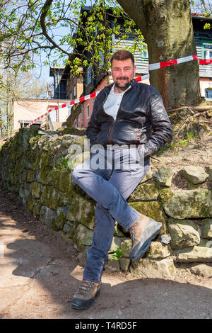 Schmilka, Germany. 18th Apr, 2019. Sven Erik Hitzer, snack bar operator on the Großer Winterberg, sits on a stone wall directly in front of the restaurant which is closed. The coming Easter weekend is expected to see a large rush of visitors to the observation tower on the Great Winter Mountain in Schmilka near Bad Schandau. However the quarrels around the closing of the catering trade on the large winter mountain as tradition restaurant are a topic, so that now a snack stall is to create remedy. Credit: Daniel Schäfer/dpa/Alamy Live News - Stock Photo