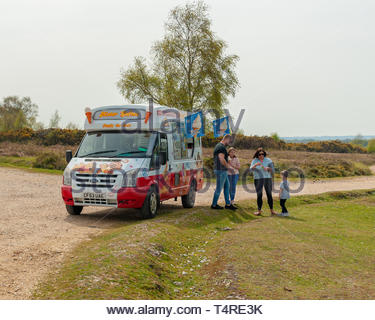 Godshill, Fordingbridge, New Forest, Hampshire, UK, 18th April 2019, Weather: An early taste of summer as temperatures break though the 20 degrees mark on Maundy Thursday ahead of an Easter weekend which is expected to be even warmer. A family buy ice creams from an ice cream van in the sunshine. Credit: Paul Biggins/Alamy Live News - Stock Photo
