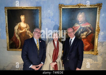 18 April 2019, Saxony, Wermsdorf: Dirk Syndram (l-r), Director of the Green Vault, Marion Ackermann, Director General of the Dresden State Art Collections, and Matthias Haß (CDU), Minister of Finance of Saxony, stand in front of portraits of Friedrich August II and Maria Josepha of Austria in Hubertusburg Palace. Europe's largest hunting lodge is to become a permanent art and cultural centre in Saxony. From 28.04.2019 to 06.10.2019, exhibits as well as sound and video installations will be shown on the occasion of the wedding of Saxony's Kurprince Friedrich August II with an emperor's daughter - Stock Photo