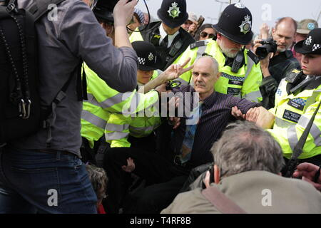 London, City of London, UK. 17th Apr, 2019. A protester seen showing a peace sign while being carried away by police during the demonstration.Protesters blocked roads demanding for the Government to take action on climate change issues during the Extinction Rebellion disruption and protests in Central London. Credit: Ben Booth/SOPA Images/ZUMA Wire/Alamy Live News - Stock Photo