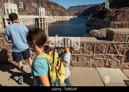 Boulder City, Nevada, USA. 23rd Oct, 2015. Tourists drink water while viewing the low waters of Lake Mead seen from the Hoover Dam. Years of unrelenting drought are straining a large reservoir of water between Nevada and Arizona. Lake Mead's water level has dropped by about 120 feet (37 meters) from where the water reached 15 years ago, on July 6, 2000. Lake Mead is no stranger to droughts. The man-made lake hit lower-than-average water levels in the mid-1950s and mid-1960s, and the current depletion is part of a decade-long trend. Lake Mead's current low level hasn't been recorded since the - Stock Photo