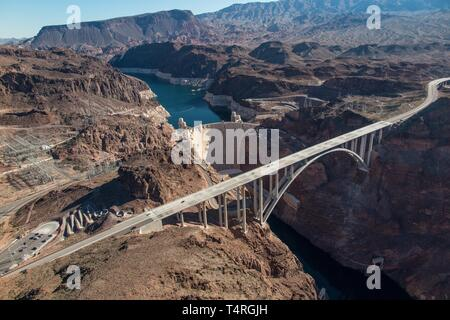 Boulder City, Nevada, USA. 23rd Oct, 2015. On the shore of Lake Mead, the Hoover Dam and its new companion, the Mike O'Callaghan-Pat Tillman Memorial Bridge in this aerial view. Years of unrelenting drought are straining a large reservoir of water between Nevada and Arizona. Lake Mead's water level has dropped by about 120 feet (37 meters) from where the water reached 15 years ago, on July 6, 2000. Lake Mead is no stranger to droughts. The man-made lake hit lower-than-average water levels in the mid-1950s and mid-1960s, and the current depletion is part of a decade-long trend. Lake Mead's cur - Stock Photo
