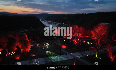 St.Goarshausen, Germany. 18th Apr, 2019. The trees of the newly designed Loreley plateau shine in the light of the light art festival 'Rheinleuchten' (aerial photograph with a drone). The redesign began in September 2016. The federal government, the state and the Loreley municipality have provisionally provided around 15.5 million euros for the redesign and renovation of the leased concert stage. Credit: Thomas Frey/dpa/Alamy Live News - Stock Photo