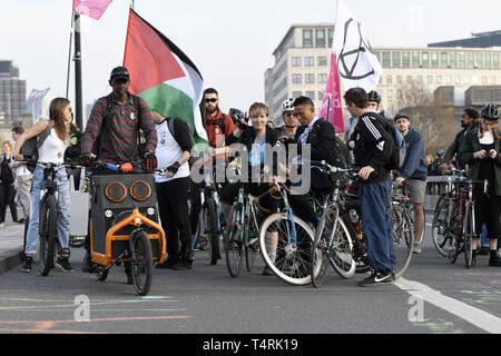 London, Greater London, UK. 18th Apr, 2019. Climate change protestors are seen with an Extinction Rebellion flag and a Palestinian flag while are waiting for the Critical Mass ride to start during the Extinction Rebellion Strike in London.Environmental activists from Extinction Rebellion movement hold for fourth consecutive day Waterloo Bridge in London. Activists has been parked a lorry on the bridge blocking the street causing disruptions. Police have been arresting protesters that refuse to head to Marble Arch. Extinction Rebellion demands from the government direct actions - Stock Photo