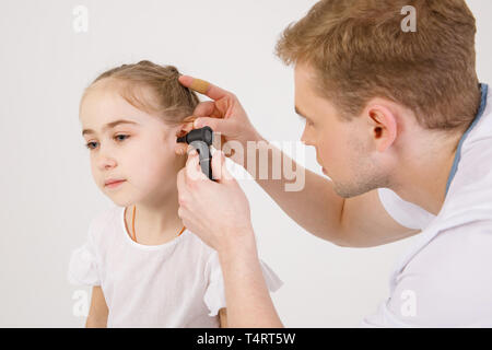 The young sympathetic otolaryngologist examines the ears of a girl - a girl of school age - Stock Photo