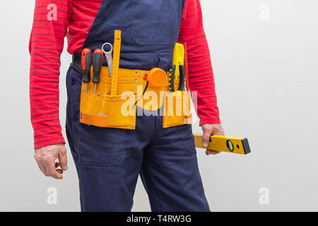 Craftsman in uniform and yellow helmet posing in front of the wall in a new home - renovation concept - Stock Photo