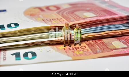 Miniature figurines,pensioner couple, sitting on euro notes,currency, - Stock Photo
