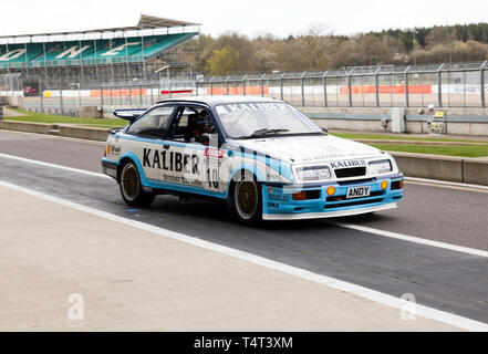 A 1989  Ford Sierra RS500  Cosworth, driven by Andy Rouse  and Guy Edwards, in the pit lane at the 2019 Silverstone Classic Media Day. - Stock Photo