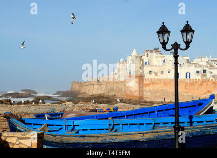 Essaouira Ramparts view with lantern and traditional blue ship in Essaouira, Morocco. Essaouira is a city in the western Moroccan region on the Atlant - Stock Photo