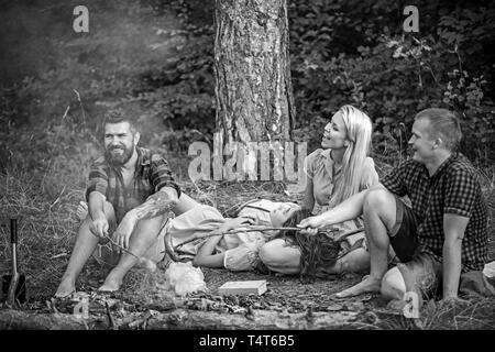 Two couples camping in woods. Guys in red lumberjack shirts cooking sausages over fire. Happy smiling people relaxing around campfire in the evening. - Stock Photo