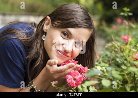 Young woman smelling roses, Germany - Stock Photo