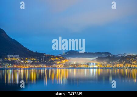 Lugano and lake Lugano with mountain and colorful sky in blue hour in Ticino, Switzerland. - Stock Photo