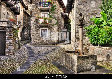 Rustic village with a water well made in stone in Arcegno, Switzerland - Stock Photo