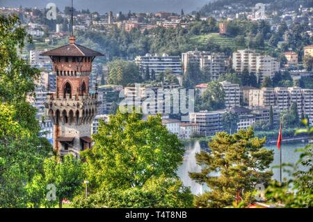 Castle and houses on the mountain with a lake in Lugano, Switzerland - Stock Photo