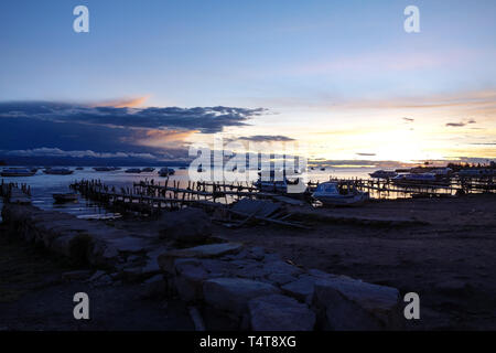 Colorful sunset above the Lake Titicaca from the shore side in Copacabana Bolivia - Stock Photo