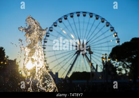 Water Fountain and Ferris Wheel with Sunset in Nice, France - Stock Photo
