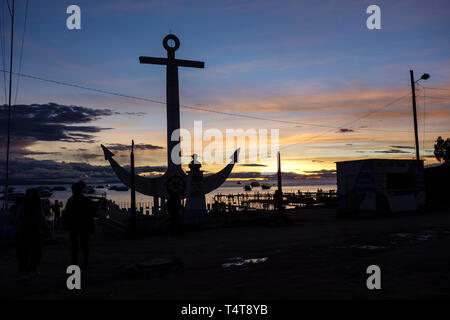 Colorful sunset above the Lake Titicaca from the shore side in Copacabana Bolivia - big anchor silhouette - Stock Photo