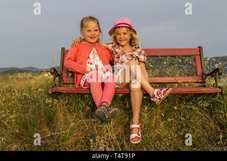 Children (5, 6) sitting on a bench, sunset, Afionas, Corfu, Greece, Europe - Stock Photo