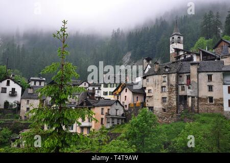 Small Village Fusio in the Mountain with Green Trees and Clouds in Ticino, Switzerland. - Stock Photo