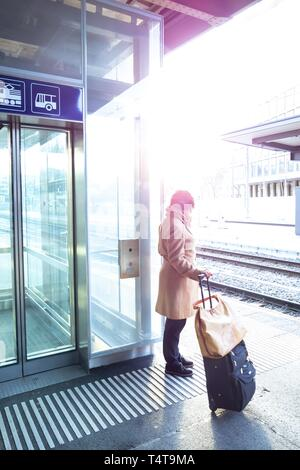 Woman with luggage, railroad station with sunlight in St Gallen, Switzerland - Stock Photo