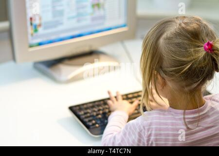 Girl (4) sitting in front of the computer monitor to see from behind, Germany, Europe - Stock Photo