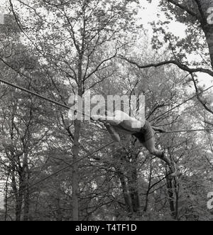 1960s, historical, a young adventure scout lying down on a rope using his hands and feet to manoeuvre himself across a clearing between two trees, England, UK. Young people in the scouts take part in many outdoor adventure activities helping develop their character's and future life skills. - Stock Photo