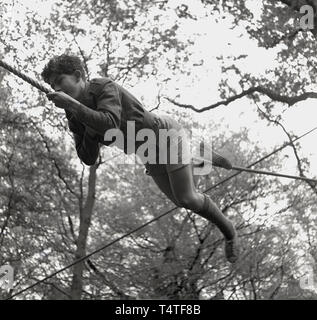 1960s, historical, a young adventure scout lying down on a rope using his hands and feet to manoeuvre himself across a clearing between two trees, England, UK. Young people in the scouts take part in many outdoor adventure activities which help to develop their character and life skills. - Stock Photo