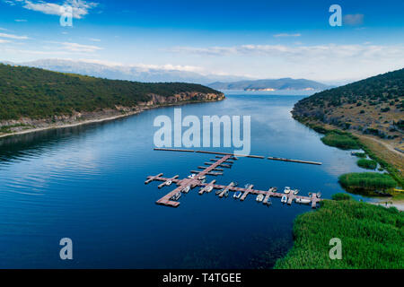 Aerial picture of floating dock with boats, motorboats and vessels floating on water in lake Small Prespes, Northern Greece - Stock Photo