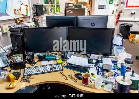 Messy desk in a workplace office. - Stock Photo