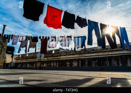 Bari, Italy - March 10, 2019: Clothes hanging from a rope drying in the sun on the roof of an old building. - Stock Photo
