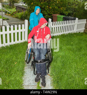 Mother with handicapped son in the rain - Stock Photo