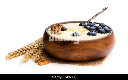 Wooden  bowl of semolina porridge with blueberry and walnut isolated on white - Stock Photo