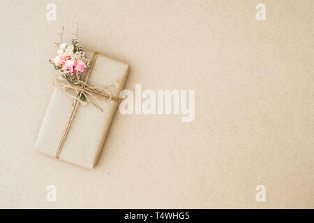 Beautiful vintage gift box wrapped in brown craft paper for holiday, anniversary, and festive events concept. Flat lay top view with copy space. - Stock Photo