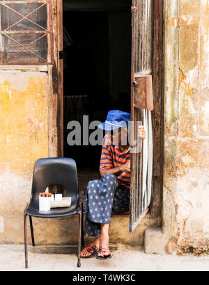 Havana, Cuba - 25 July 2018: A man sits in the doorway of his home selling cigars to earn extra income. - Stock Photo