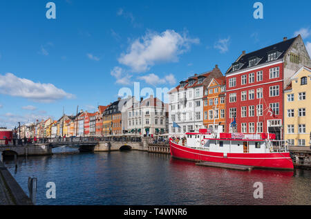 Big red boat moored in a canal in Copenhagen, long row of typical Danish colored houses on a beautiful sunny day with a blue sky and some white clouds - Stock Photo