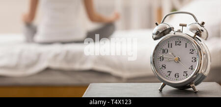 Woman meditating with alarm clock on foreground - Stock Photo